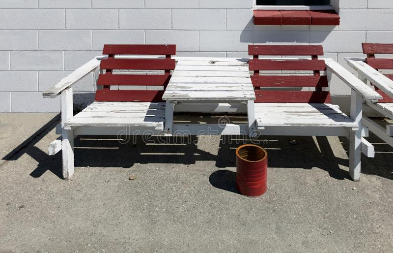 Maroon and white color painted wooden outdoor summer bench chair against white brick concrete block wall background and red bucket. As an cigarette ashtray stock images