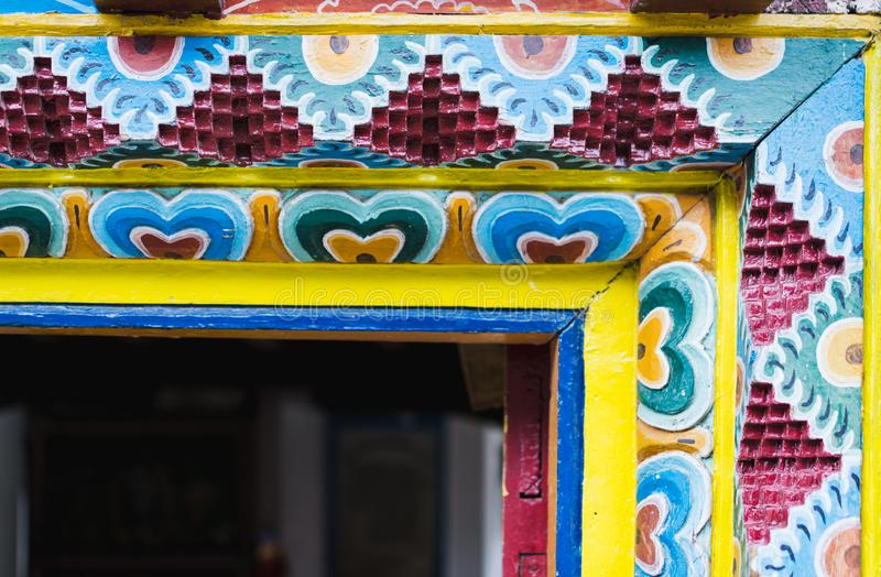 MARPHA, NEPAL - MAY 2015: Detail of wood carving on Nepalese Buddhist monastery entrance door. MARPHA, NEPAL - MAY 2015: Detail of wood carving ornament on royalty free stock photography