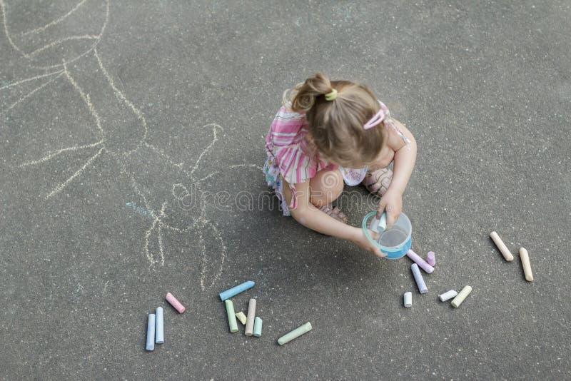 Marquage à la craie de trottoir de la petite fille blonde utilisant la jupe rose de ruche image stock
