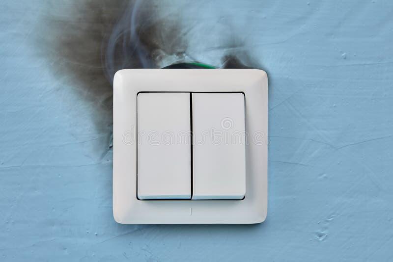 Marque de fumée et de brûlure sur l'interrupteur de lampe électrique images stock