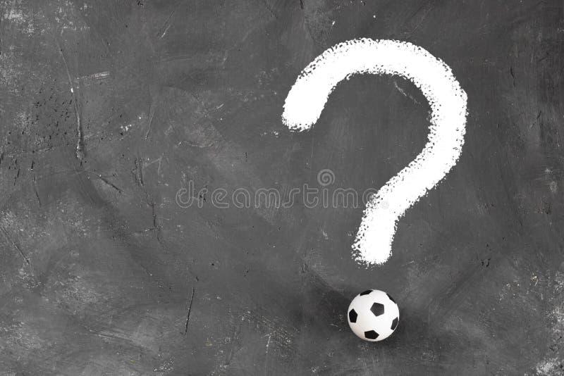 Marque de Quastion faite en petite boule du football et ligne de craie blanche sur le fond texturisé foncé de tableau noir avec l photos stock