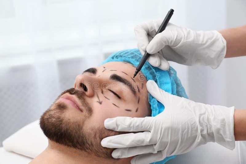 Marques de dessin de docteur sur le visage de l'homme pour l'opération de chirurgie esthétique dedans photographie stock libre de droits