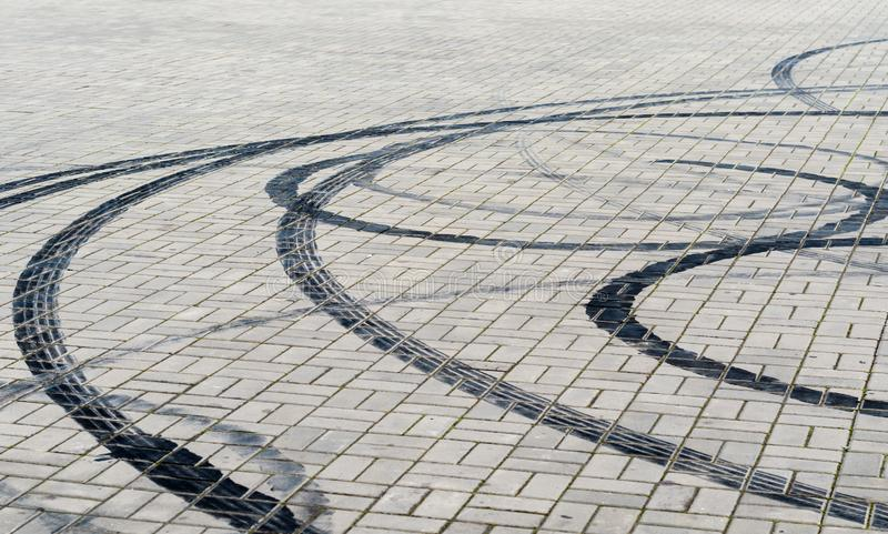 Marques noires des pneus de freinage sur des roues de voiture sur la route photo libre de droits