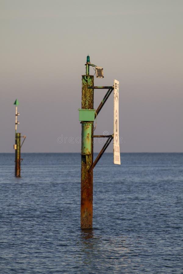 Marqueur rouillé de canal en mer avec l'eau et le ciel calmes photographie stock