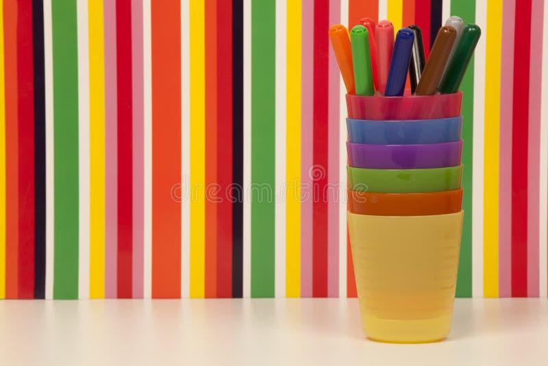 Marqueurs colorés, tasses en plastique empilées et fond multicolore de rayures images libres de droits