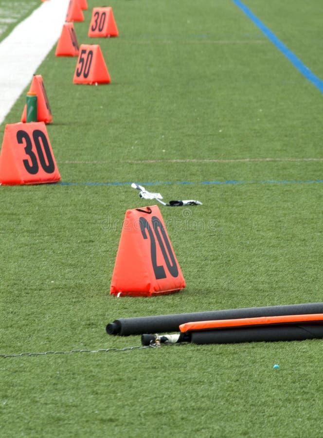 Marqueurs oranges de champ sur le terrain de football photographie stock libre de droits