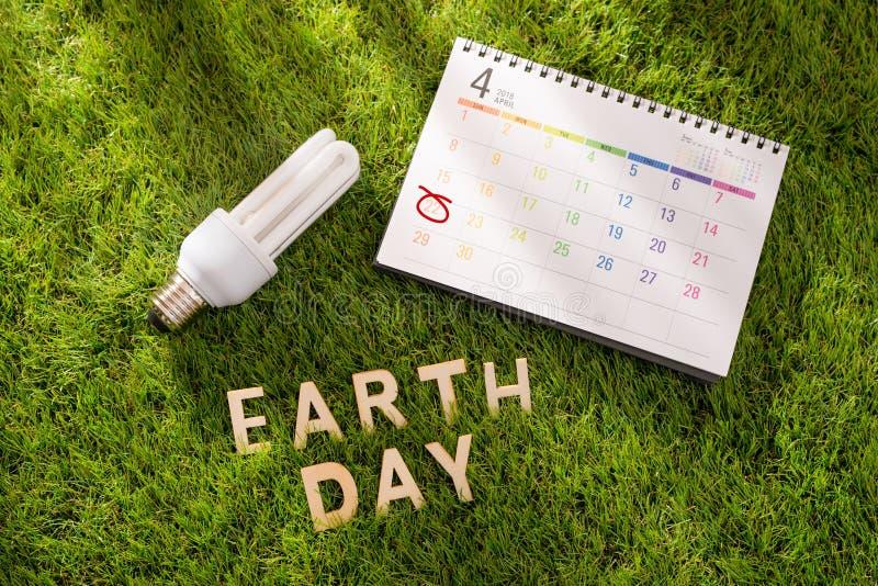 Marquez avec des lettres le concept heureux de jour de terre avec le calendrier sur l'herbe verte images stock