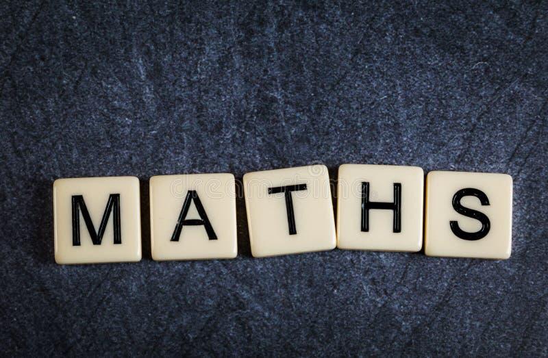 Marquez avec des lettres les tuiles sur des maths noires d'orthographe de fond d'ardoise images stock