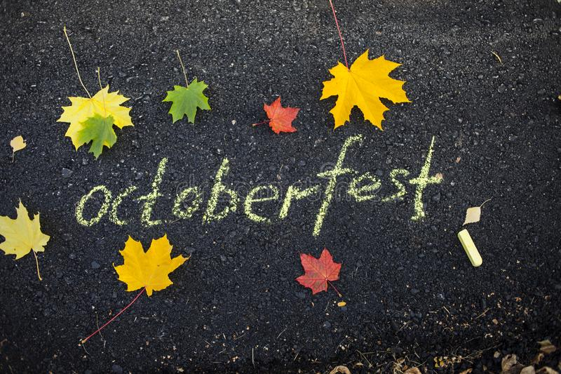 Marquez l'inscription à la craie sur les feuilles d'automne d'Oktoberfest d'asphalte sur le trottoir images libres de droits