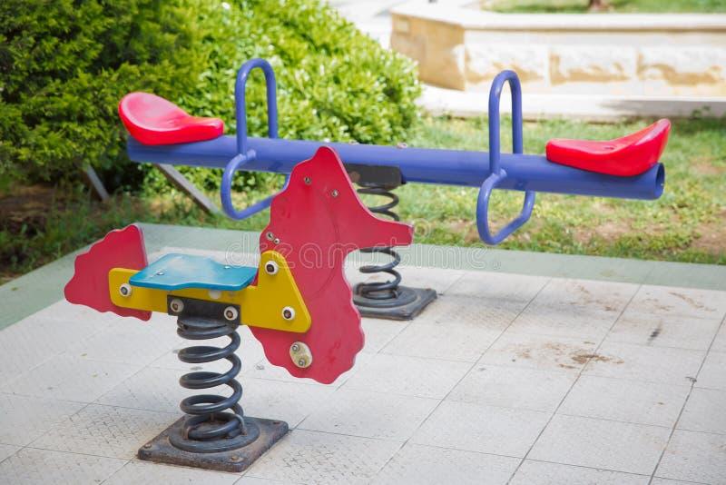 Marra no recreio infantil no parque cavalo para crianças no recreio Balançar numa espiral metálica Cavalo da primavera no playgro imagens de stock