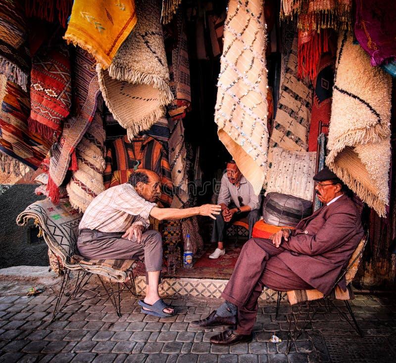 MARRAKECH, МАРОККО, ИЮНЬ 2016: Уличные торговцы обсуждая внутри для стоковая фотография