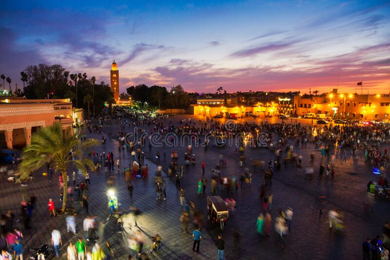 MARRAKECH, MOROCCO - APR 29, 2016: Sunset view on the Koutoubia mosque and Djemaa el Fna square with people in Marrakesh royalty free stock photos