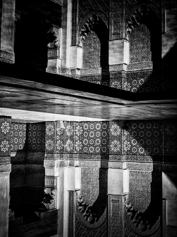 Marrakech, MOROCCO - February 10, 2012 - Courtyard carvings water reflexions in Ben Youssef Madrasa stock photography