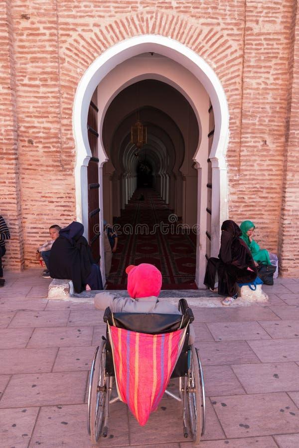Marrakesch, Marokko - 13. März 2018: Ein Mann in den Wartezeiten eines Rollstuhls am Eingang der Koutoubia-Moschee, damit jemand  lizenzfreie stockbilder