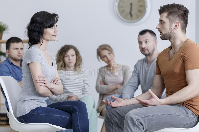 Marriage counseling session. Couple talking about their relationship problems in front of other people during a marriage counseling session stock images