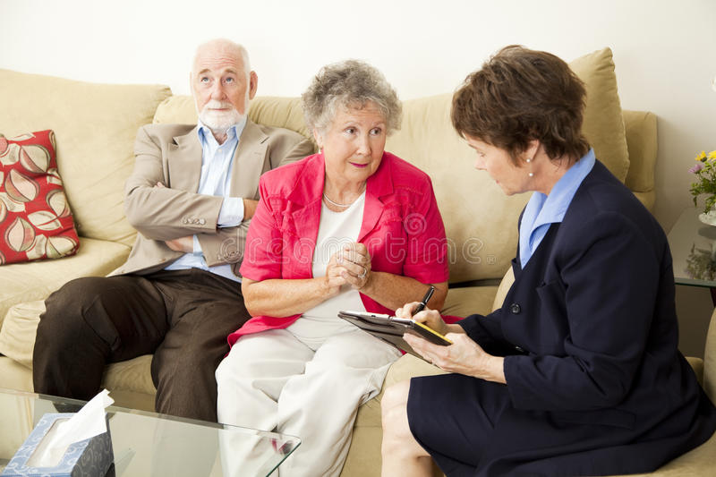Marriage Counselng - Can You Help Us. Senior couple in marriage counseling. The wife talks while the counselor takes notes stock photo