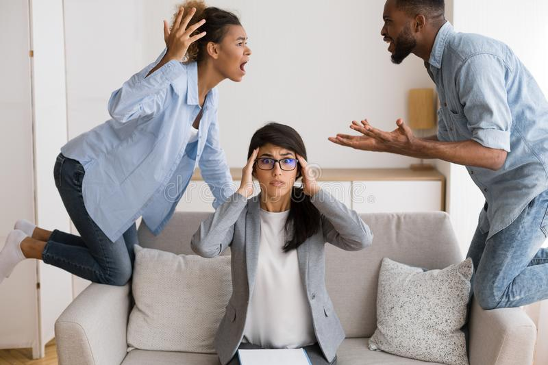 Shocked Marriage Counselor Watching Her Afro Patients Quarrelling In Office. Marriage Crisis. Overwhelmed Psychologist Watching Her Afro Patients Quarrelling In royalty free stock images