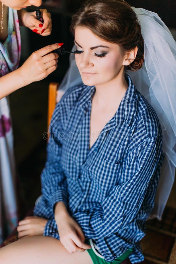 Marriage day moment. Applying make-up for beautiful young bride in dressing room stock photo