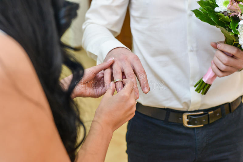 Marriage hands with rings. birde wears the ring on the finger of the groom. Birde wears the ring on the finger of the groom stock image