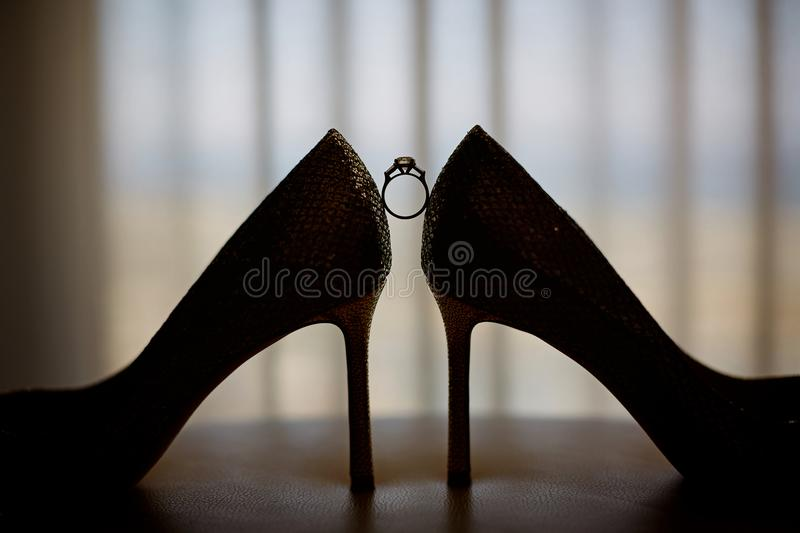 Marriage proposal. Golden wedding rings and engagement ring near luxury bridal shoes on high heels. Best view for bride at wedding stock photos