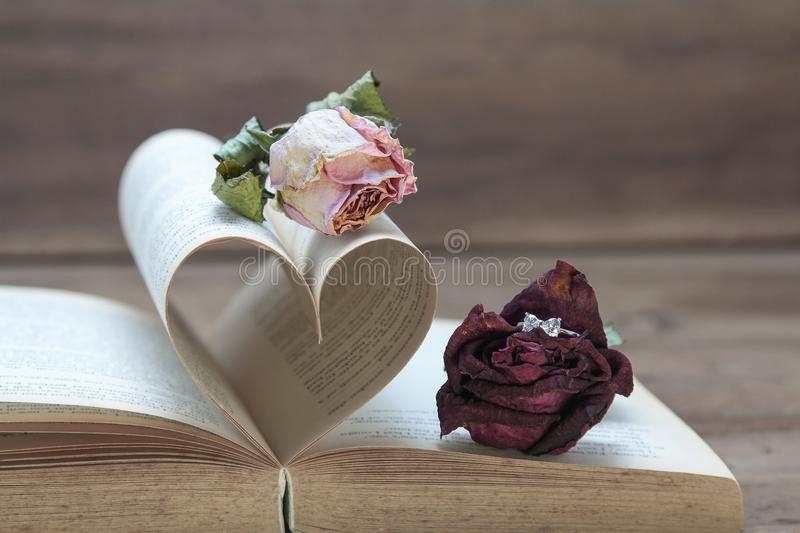 Marriage proposal, love concept with rose, ring and old book in heart shaped. stock photos