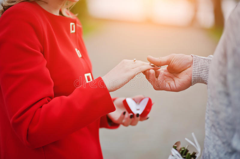 Marriage proposal. Man hold engagement ring at red box in his ha royalty free stock images