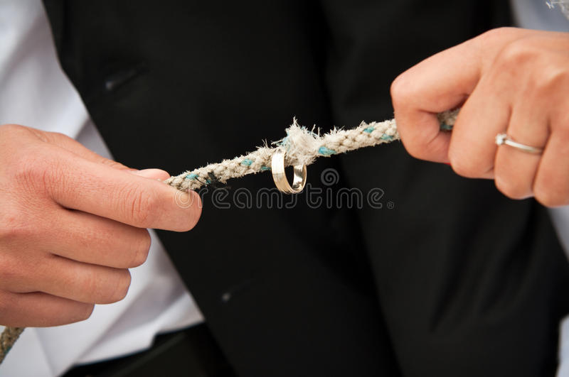 Marriage strength. Conceptual image showing a marriage strength or weakness - the wedding ring on worn rope, held by groom and bride stock photography