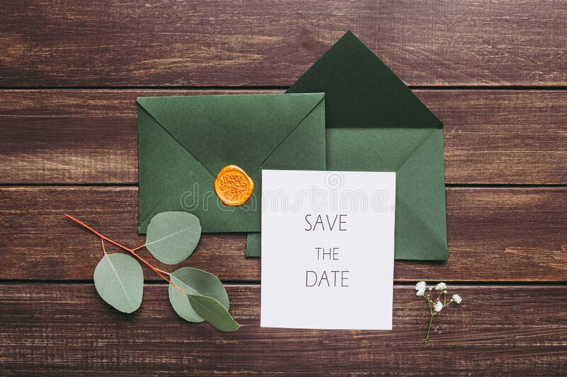 Marriage or Wedding Green envelopes with postcard inside. Save the date invitation. Marriage or Wedding Green envelopes with postcard inside on wooden background stock photos