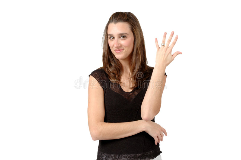 Married. Woman holds up her hand and shows off her wedding ring. SHe may be telling the guys to back off, she's taken. Or just proud to show off her ring stock image