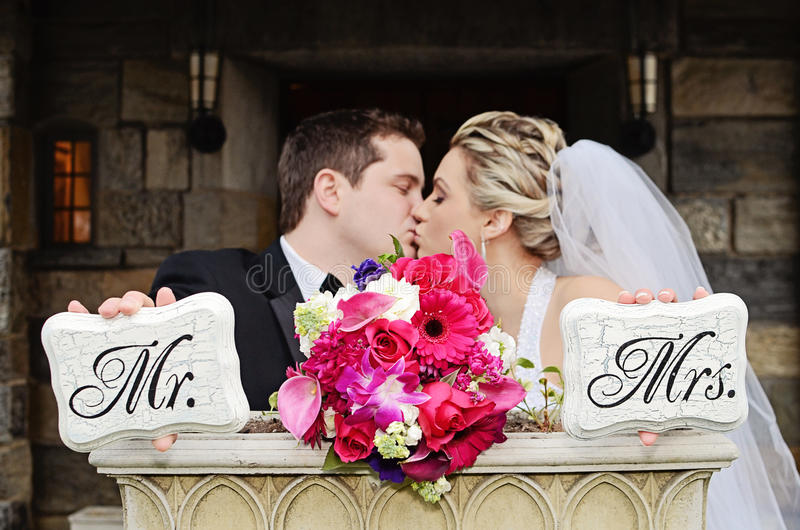 Married couple. A bride and groom kissing holding Mr and Mrs signs stock image