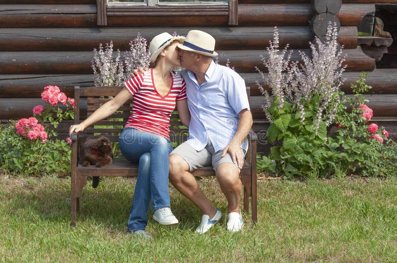 Married couple aged kissing on a bench in the village royalty free stock photo