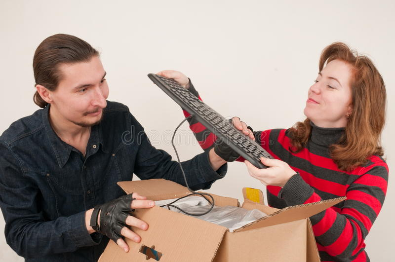 Married couple and box. The married couple has opened a cardboard box where the computer is packed stock images