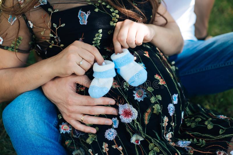 A married couple is close-up, the husband is hugging his pregnant wife for the stomach. Family is waiting for the birth royalty free stock photo