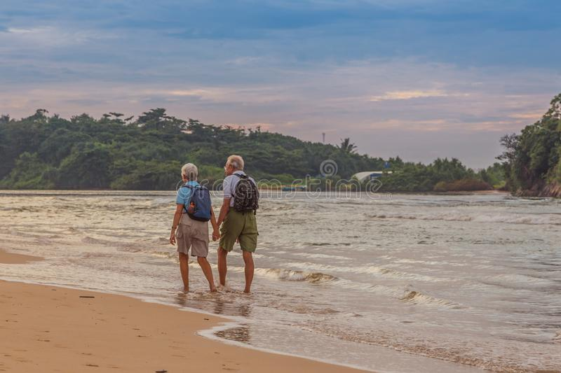 Married couple of elderly people on the beach on the ocean shore stock photos