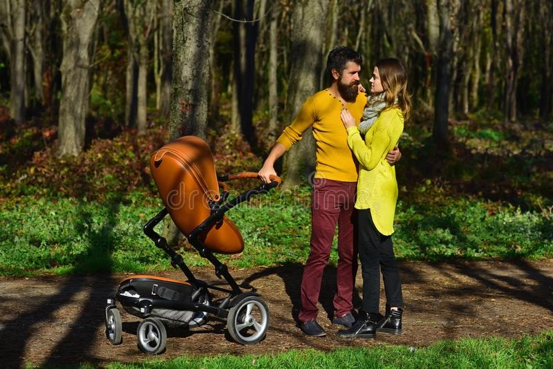 Married couple enjoy walking in spring park with baby pram. Family enjoy sunny day outdoor. Find what brings you joy and stock photos
