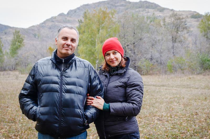 Married couple of forty years in autumn clothes in the mountains royalty free stock images