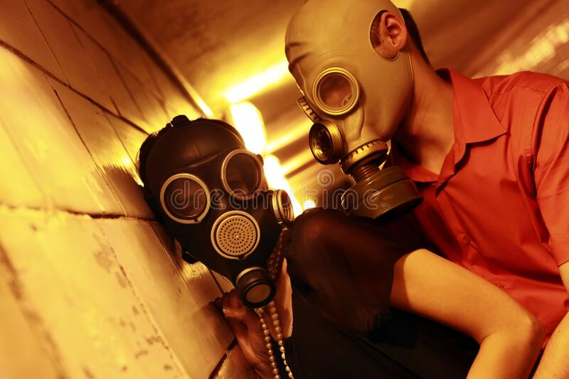 Married couple in gas masks in a tunnel.  royalty free stock photos