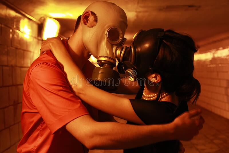 Married couple in gas masks in a tunnel.  stock images
