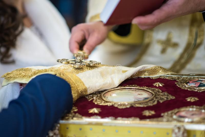 Married couple gives a vow of loyalty in the temple, Christian traditions. Married couple gives a vow of loyalty in the temple holding hands on the bible, priest royalty free stock photo
