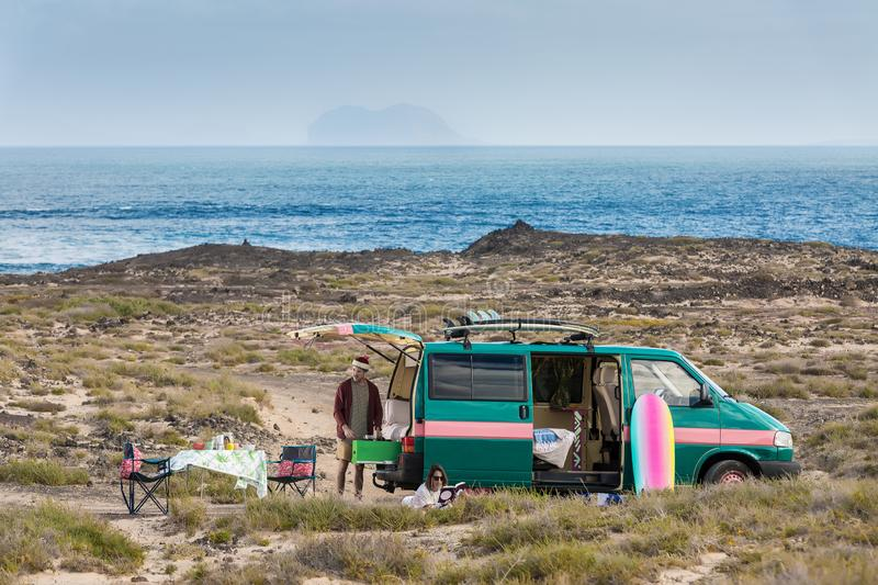 Married couple having caravan trip on seacoast. Man and woman spending time in leisure while having camping van trip on shoreline of Lanzarote island, Spain stock photo