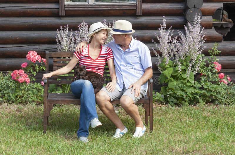 Married couple with his cat sitting on a bench stock photography