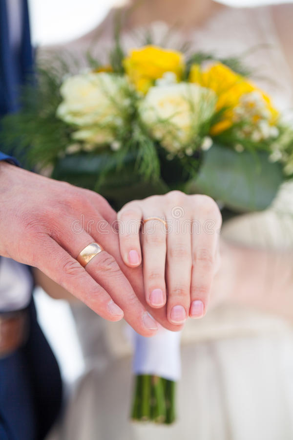 Married couple hold their hands with wedding rings stock photo