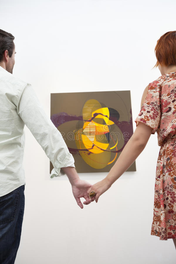 Married couple holding hands in front of painting in art gallery stock photography