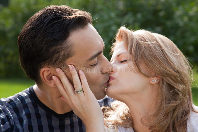 Married couple kissing outdoors. Day stock photo