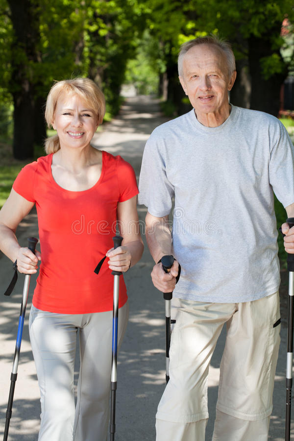 Married couple practicing nordic walking stock photos