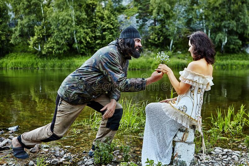 Married couple resting in nature. A brutal shaggy man, dressed in camping clothes, gives a bouquet of wildflowers to a women in an evening dress, amid wildlife royalty free stock photo