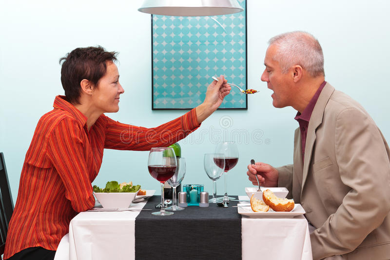 Married couple sharing food in a restaurant royalty free stock photo