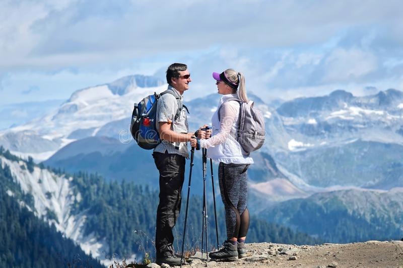 Married couple travelling in mountains. Young man and woman standing on cliff looking at each other with beautiful view behind royalty free stock photography
