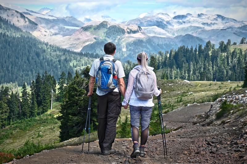 Married couple walking in mountains with backpacks and hiking poles. stock photos