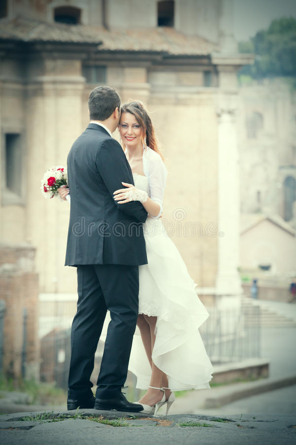 Married couple with wedding dress in the city. Married couple with wedding dress are embraced in the historic center of Rome, Italy. The bride holds a bouquet of stock image